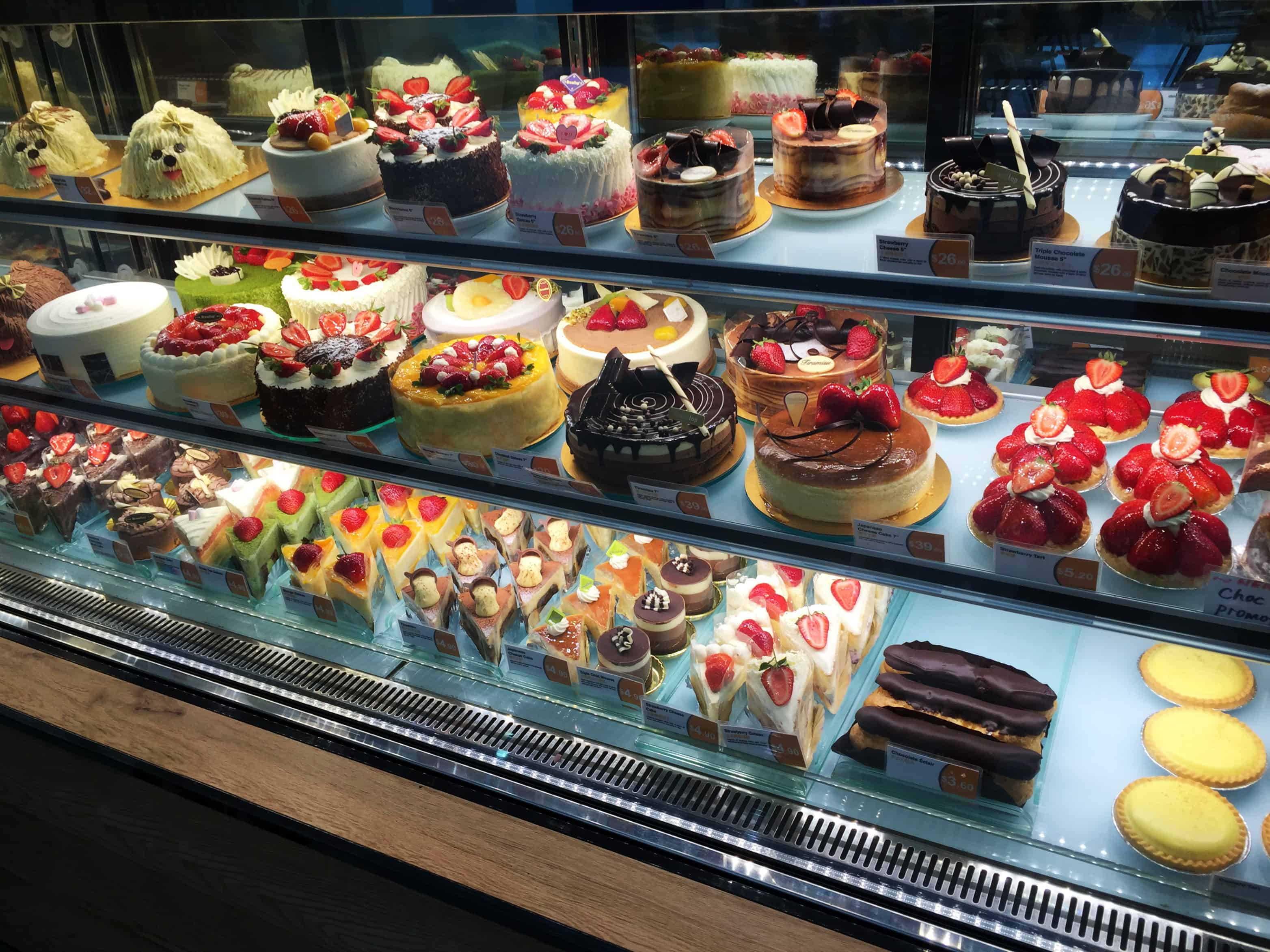 Cakes and bakery items displayed in glass shelf